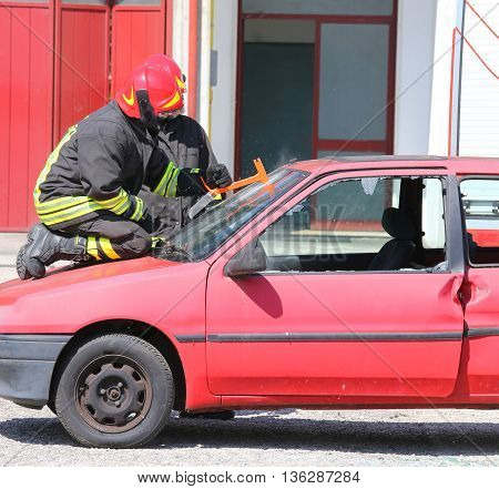 Firefighter Cuts The Windshield  Of Car With A Hacksaw