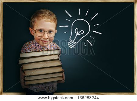 Boy with books near school chalkboard having come up with the brilliant idea
