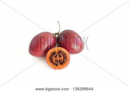 Deep red tamarillo tree tomato sliced and whole isolated on white