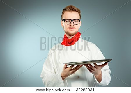 Portrait of a male chef cook in uniform holding empty tray. Copy space. Occupation. Studio shot.