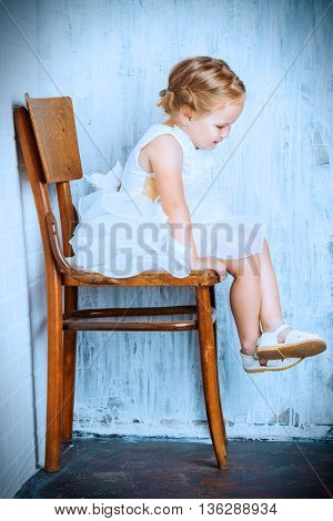 Cute little girl in a beautiful white dress sitting on the old chair by the white brick wall. Childhood.