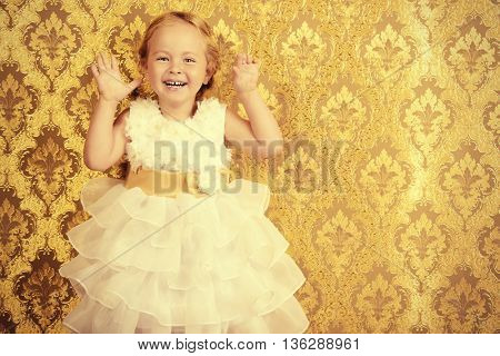 Happy little girl in a beautiful white dress standing by the vintage wall. Childhood. Holiday, birthday.