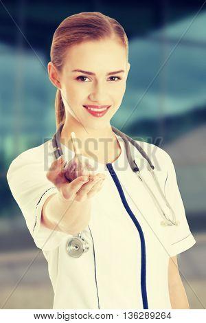 Beautiful nurse or doctor is holding raw garlic.