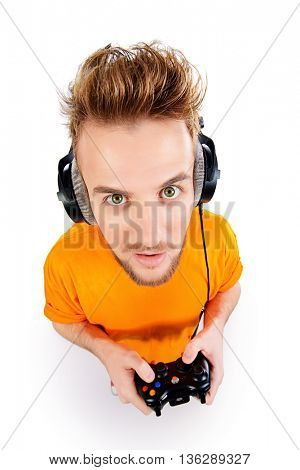 Crazy gamer with controller and headphones. Isolated over white.