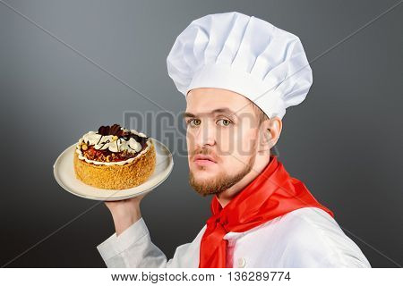 Portrait of a funny male confectioner going to throw a cake.