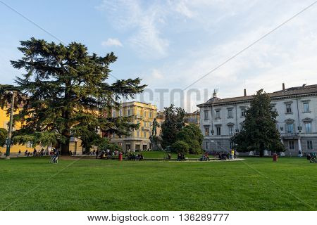 people relax near grassland and european style buildings in switzerland