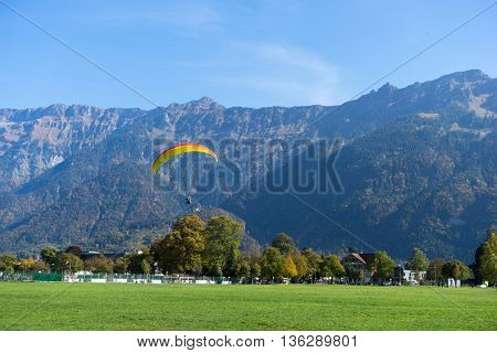 beautiful paragliding field near alpes mountain in switzerland in blue sky