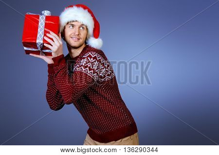 Attractive young man in Santa Claus cap holding a gift box and smiling. Christmas celebration.