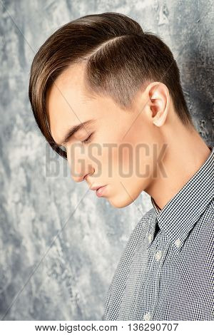 Portrait of a young man with fashionable hairstyle.