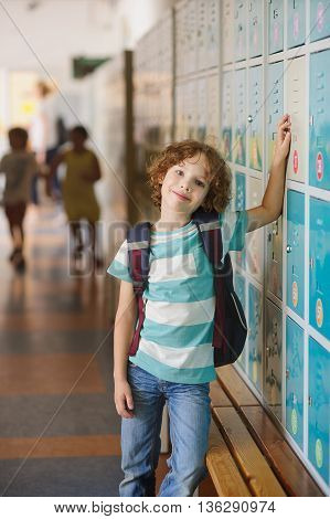 Little learner standing near lockers in school hallway. He put his hand on my locker. The boy with a wistful smile looking at the camera.