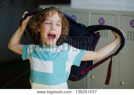 Tired little student standing in the hall near the lockers and wears a backpack. The boy yawns.