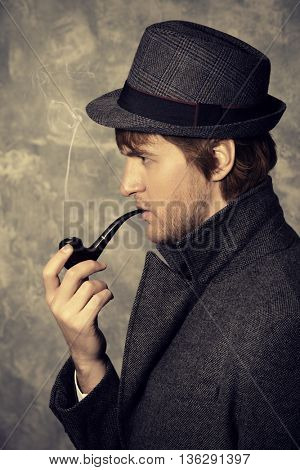 Handsome young man wearing classic hat and a coat smokes a pipe. Beauty, fashion. Side view.