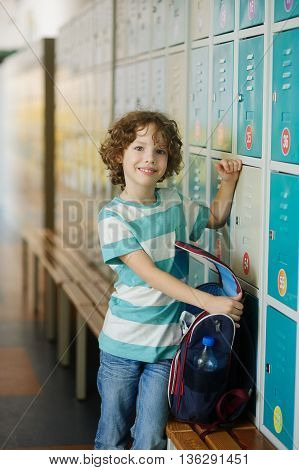 The schoolboy standing near lockers in school hallway. He opened the backpack to shift something in the locker. The boy has blond curly hair and blue eyes. He smiles.