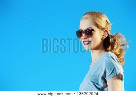 Portrait of a happy smiling young woman in sunglasses over blue sky. Beauty, fashion. Sunny summer day.