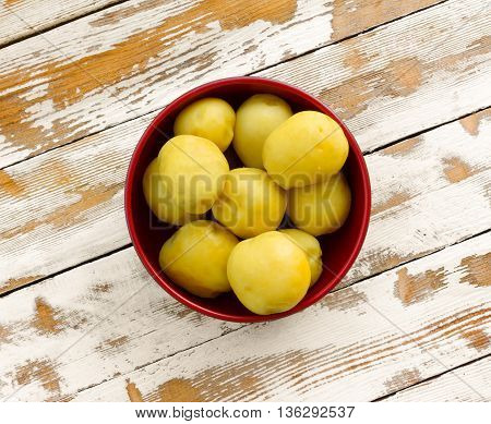 purified boiled yellow potatoes in a red bowl on the old wooden table with the remnants of white paint closeup top view