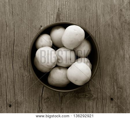 purified boiled potatoes in a circular plate on an old wooden table with cracks closeup top view. a monochrome image