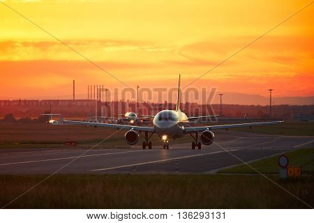 Airport traffic at the golden sunset. Airplanes are taxiing to the runway for take off.