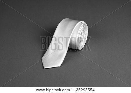 Beige necktie on gray background roll of necktie on gray background. A beige tie on gray background