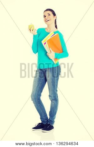 Beautiful young student with files and apple.