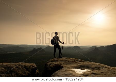 Tourist On Cliff Edge With Pole In Hand And Backpack