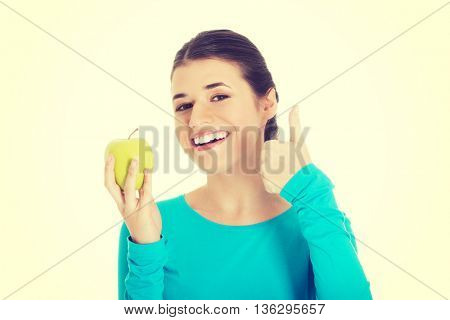 Portrait of a beautiful woman showing ok with apple.