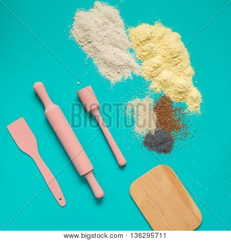 Kitchen utensils baking accessories pink rolling pin spatulaboard and flour with spices on a turquoise background.