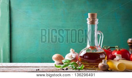Food background or healthy concept with olive oil fresh basil pasta tagliatelle mushrooms and pepper on a wooden background horizontal with copy space