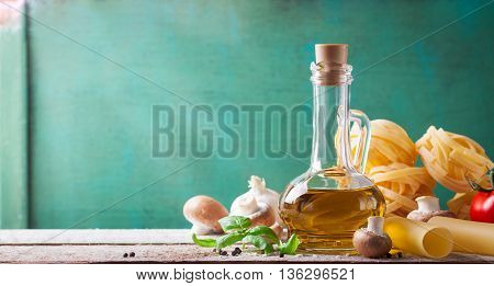 Food background or healthy concept with olive oil fresh basil pasta tagliatelle mushrooms tomatoes and pepper on a wooden background horizontal with copy space