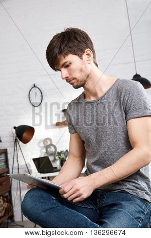 Young man using tablet computer at home.