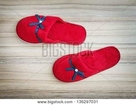 Red slippers with blue ribbon on the wooden background. Beauty and fashion. Retro style. Vibrant colors. Indoor slippers.
