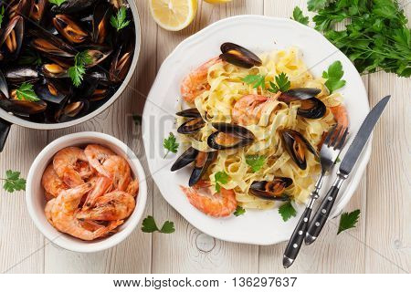 Pasta with seafood on wooden table. Mussels and prawns. Top view