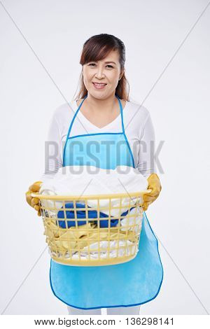 Smiling housewife holding basket with dirty clothes