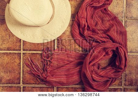 Straw hat panama hat with a red scarf lying on the tiled brown background. Horizontal image.