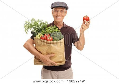 Cheerful senior holding a bag of groceries in one hand and a single tomato in the other isolated on white background