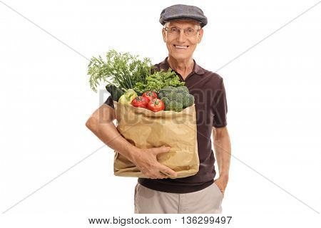 Elderly man holding a bag of groceries and looking at the camera isolated on white background