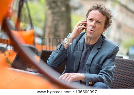 Portrait of a middle age businessman siting on the terrace of a coffee shop and speaking on the phone.