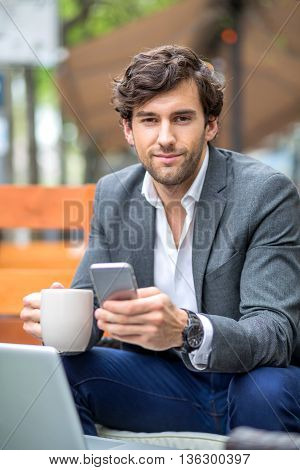 Portrait of a handsome young businessman siting on the terrace of a coffee shop.