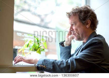 Portrait of a middle age businessman siting in the window of a coffee shop and speaking on the phone