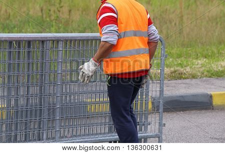 Worker With High Visibility Reflective Jacket Moves Iron Hurdles
