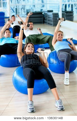 People exercising at the gym with weights and pilates ball