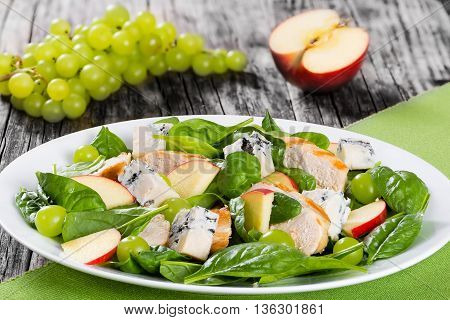 grilled chicken breast grapes spinach gorgonzola cheese and apple salad on a white dish on a table mat on dark wooden background view from above close-up