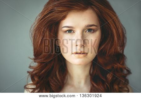 Beautiful young redhead woman with freckles portrait with curly hairdress