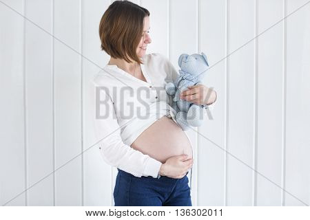 Pregnant woman profile holding a teddy bear