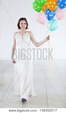 Happy young pregnant woman with colorful balloons