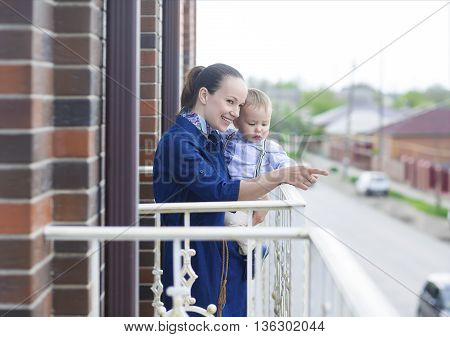 Happy young mother with baby boy on the balcony