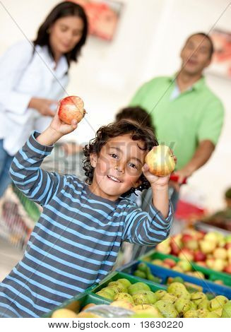 Familia en el supermercado de las compras de algunas frutas