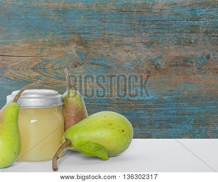 Three pears and pear juice in vintage glass jar