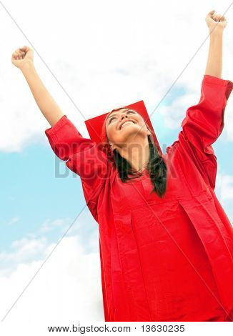 Happy graduated woman in red gown outdoors
