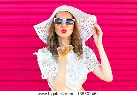 Woman In Summer Straw Hat Sends An Air Kiss Over Colorful Pink Background