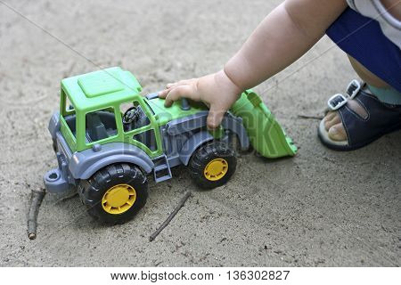 Part of the image of a small child sitting in the sand and plays with a green toy construction vehicles. Visible hand that controls the machine.